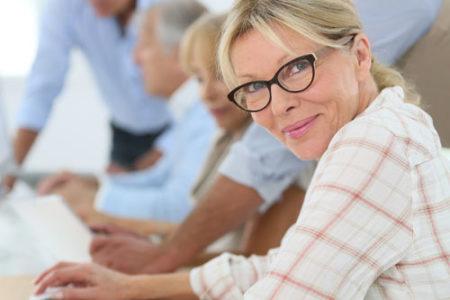 Uśmiechnięta kobieta w starszym wieku uczy się obsługi komputera